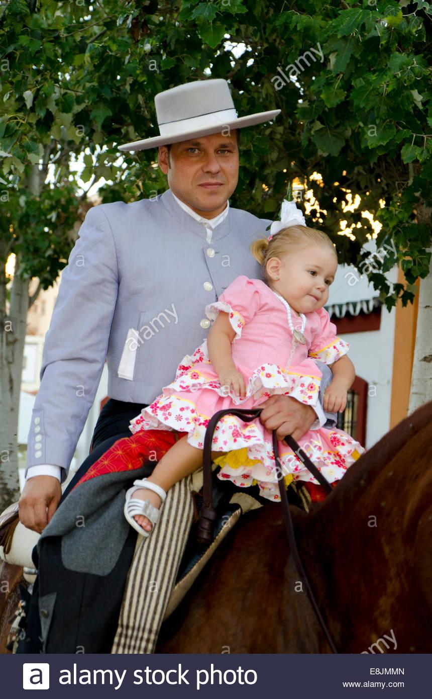 man-on-horse-wearing-cordobes-hat-in-traditional-costume-holding-girl-E8JMMN.jpg
